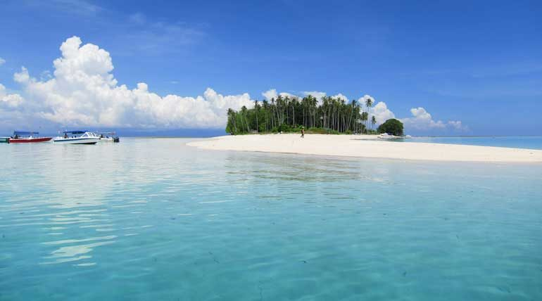 Coconut trees dot the white sandy beaches around Sibuan Island.